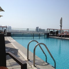 Photo taken at Hilton Dubai Roof Pool by Larissa V. on 11/4/2013