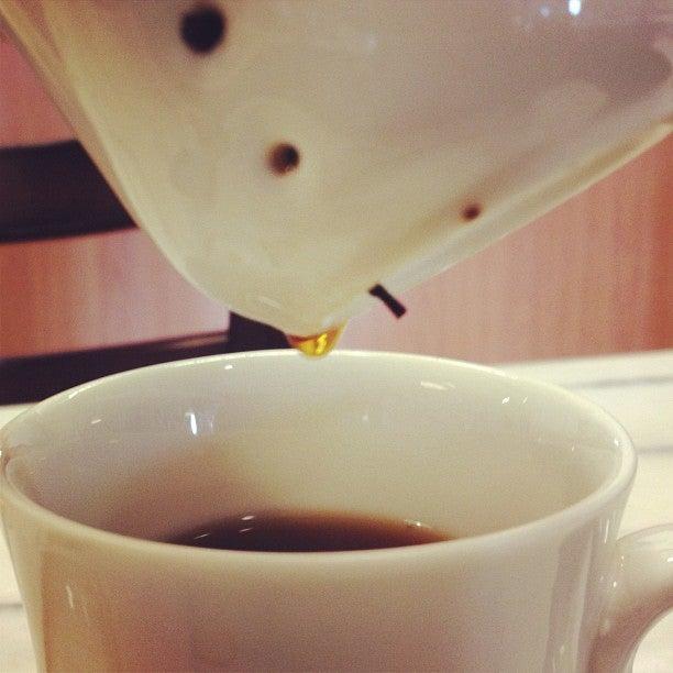 Pu-erh tea leaves in a strainer, served in a mug.
